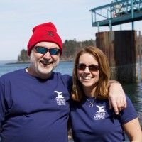 Allied Whale Research Associate Tom Fernald '91 and Assistant Registrar Mindy Viechnicki wearing the t-shirts and knit beanie at the COA Pier.