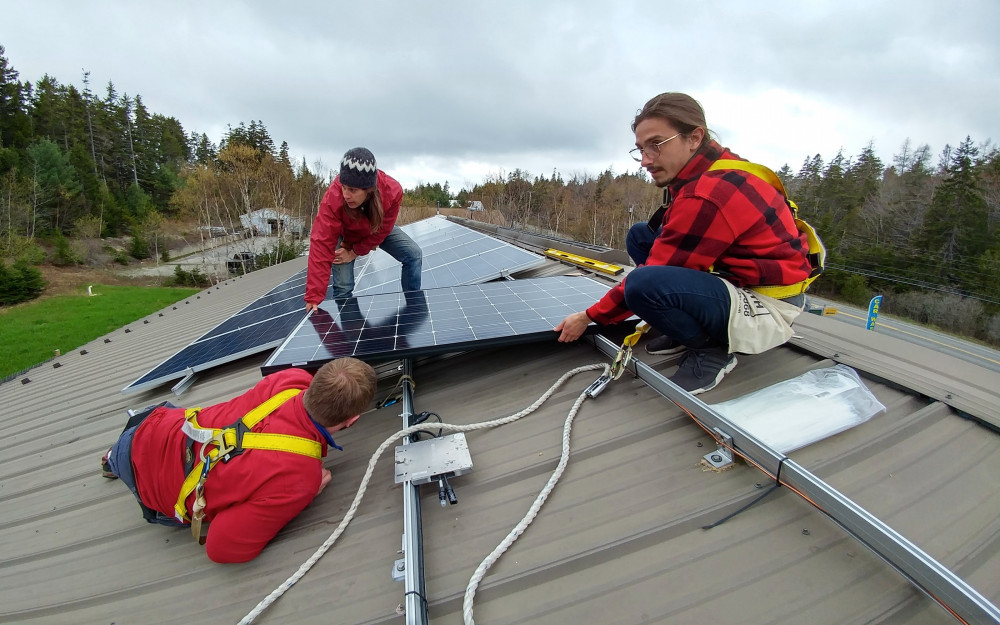 College of the Atlantic student Agim Mazreku '20, right, joins others installing solar panels on a business in one of the communities near COA's Bar Harbor campus. Sustainability education at College of the Atlantic integrates community involvement and real-world experiences with academic work.
