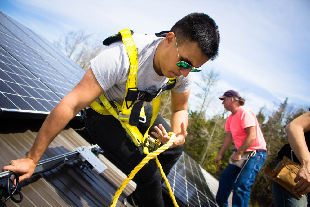 College of the Atlantic students work with COA's Community Energy Center to install solar panels on a nearby business.