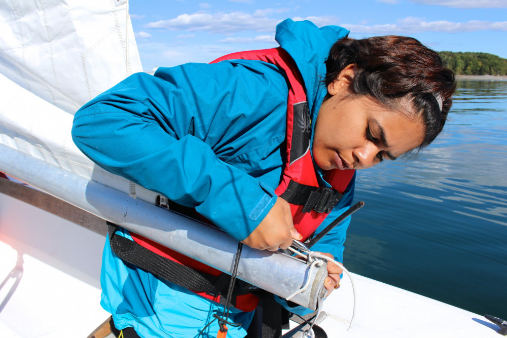 "College of the Atlantic sailing program participant Priyamvada Chaudhary '20 tries her hand at sailboat maintenance during College of the Atlantic's new sailing program. COA offers many <a href=""/our-community/student-activities/outdoor-programs/"" target=""_blank"" rel=""noopener noreferrer"">opportunities</a> for students to engage with the beautiful natural world surrounding the college."