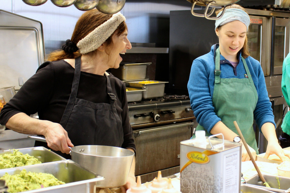 Indigo Woods '21, right, and Lise Desrockers, left, co-director of food services, work on a dis...