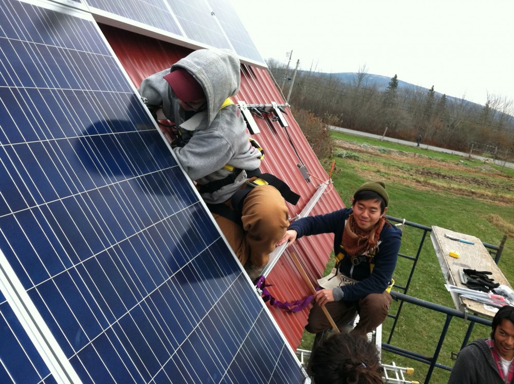 "Students install solar panels on a rooftop at College of the Atlantic's Beech Hill Farm. Through courses such as ""Practicum in Renewable Energy"" and ""The Physics and Math of Sustainable Energy,"" sustainability is central to the College of the Atlantic curriculum."