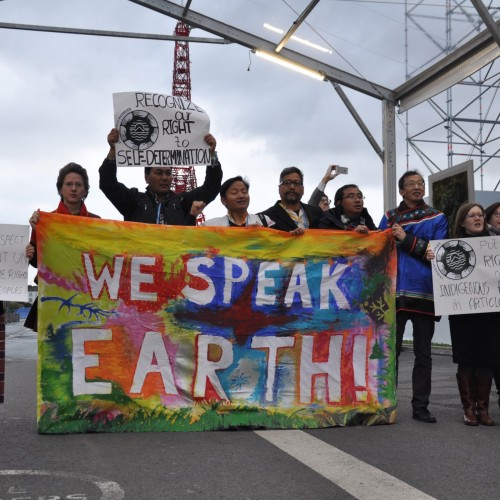 A group of activists share their message at the COP21 in Paris, 2015.