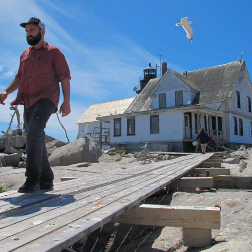 College of the Atlantic student Elijah Santner walks along a boardwalk away from the former lightkeepers' house on Mount D...