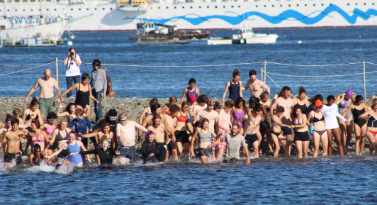 Swimmers make their way into the water from the Bar Island sand bar.