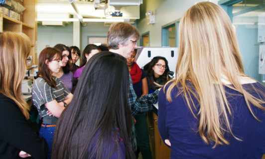 <em>Students gather around instructor Jim Coffman to view a sea urchin embryo, projected onto a computer by a microscope.</em>