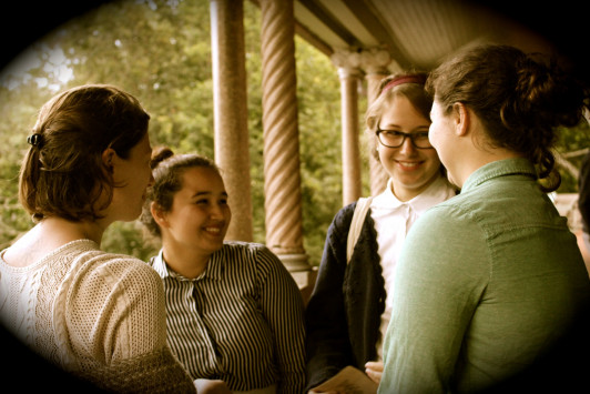 First-year students Beatrice Butler, Nichole Francia, Heather Sieger, and Laurel Streeter chat on the porch of Turrets during a 1907 reenactment dinner.