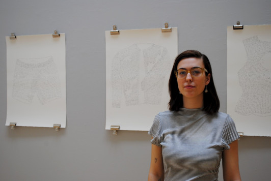 "Maya Critchfield '16 in front of ""Text(iles),"" a series of drawings that represent cl..."