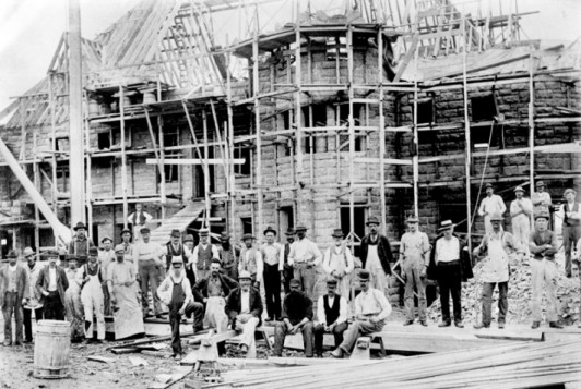 Workers gather in front of COA's historic Turrets cottage during construction in 1895