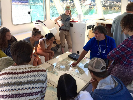 Professor John Anderson points out map locations to a group of Human Ecology Core Course students aboard <em>RV</em> <em>Osprey</em>. <em>Osprey</em> First Mate Emma Flaherty '17 stands to the left.