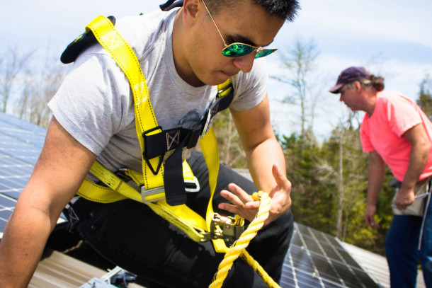 "A College of the Atlantic student working with the school's <a href=""/cec/"">Community Energy Center </a>helps install solar panels on the roof of a nearby business."
