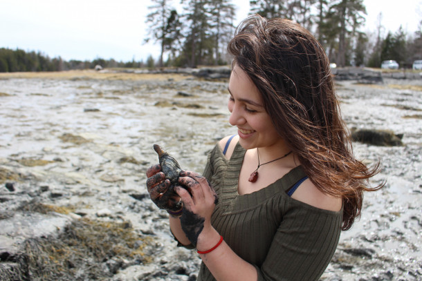 Talya Benzer-Shuman '21 observes a clam on the mudflats at Hunters Beach in Acadia National Park. Trips such as these allow students in COA's Oceanography course to pick up practical experience with some of the many organisms that make these ecosystems unique.