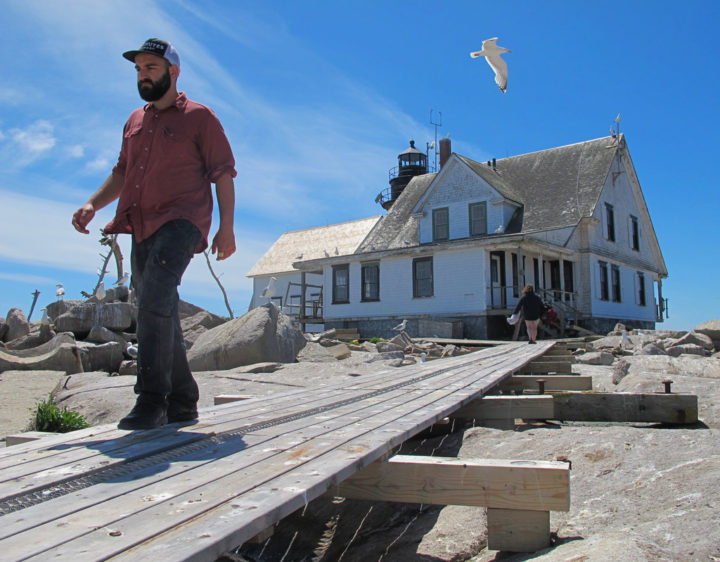 College of the Atlantic student Elijah Santner walks along a boardwalk away from the former lightkeepers' house on Mount Desert Rock on June 2, 2018. Santner is working this summer as the food services coordinator at COA's research station on the small remote island, which is 20 miles south of Mount Desert Island in the Gulf of Maine.