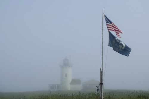 Fog rolling in partially obscures the lighthouse on Great Duck Island, but doesn't touch the flagpole.