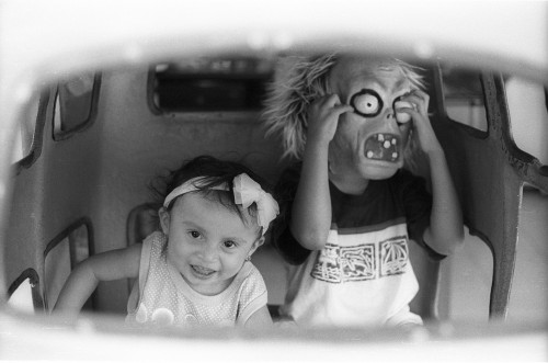 Zoe and Matias, the children of Becca's colleagues in the Centro Cultural RealizArte, play with a mask inside a toy car at...