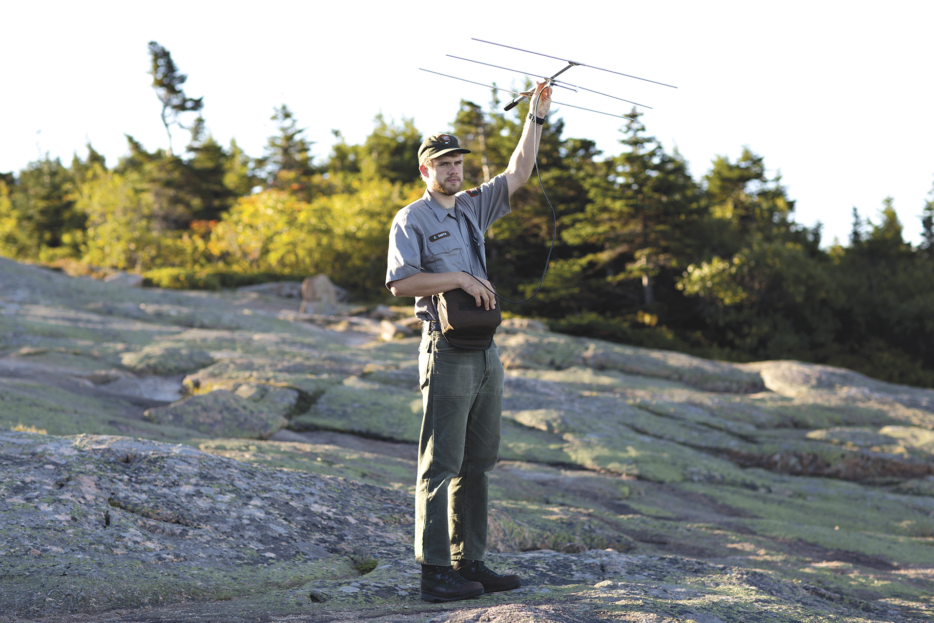 Erickson Smith '15 raises a portable receiver capable of hearing and tracking bats at the Blue Hill overlook on Acadia�...