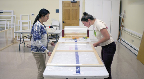 Together, Ana Zabala '20, left, and Gillian Welch '19, right, stretch plastic over the frame of a window insert to cre...