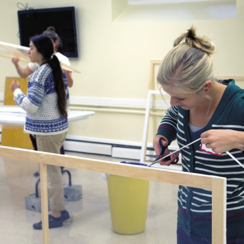 Kali Lamont '18 seals a window insert destined for a member of the Mount Desert Island communit...