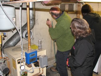 Examining a Maine homeowner's basement insulation during an energy audit.